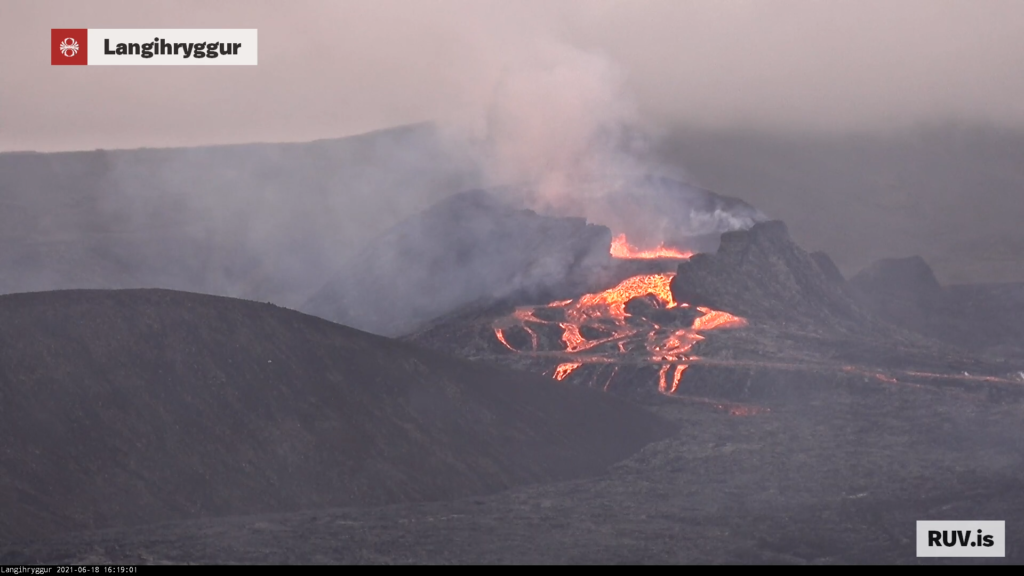 Yellow lava flows out of the crater into a lava field and creates a new lava river.