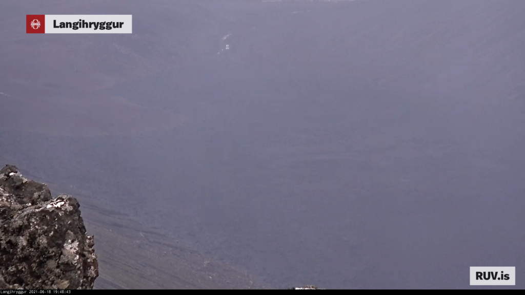 A lot of smoke blocks the clear view into Nátthagi where the lava field is and is about to leave Nátthagi. Car can be seen at the end of the lava field.