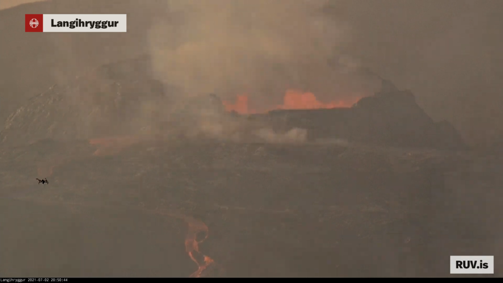 Red hot lava from the crater flows down on Rúv web camera. Small drown is in frame of the shot.