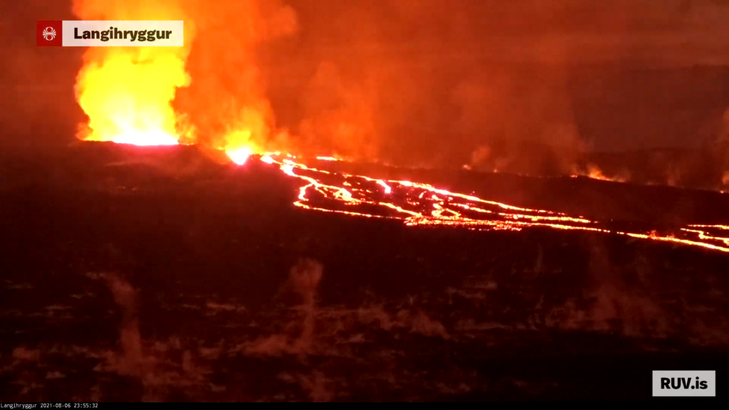 Red glow from the crater lights up the nearby lava field that has three gas funnels rising up from it. Lava is flowing from the crater down into nearby Meradalir and some of the lava is flowing underground